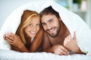smiling-couple-under-the-blanket-in-the-bed_1098-278